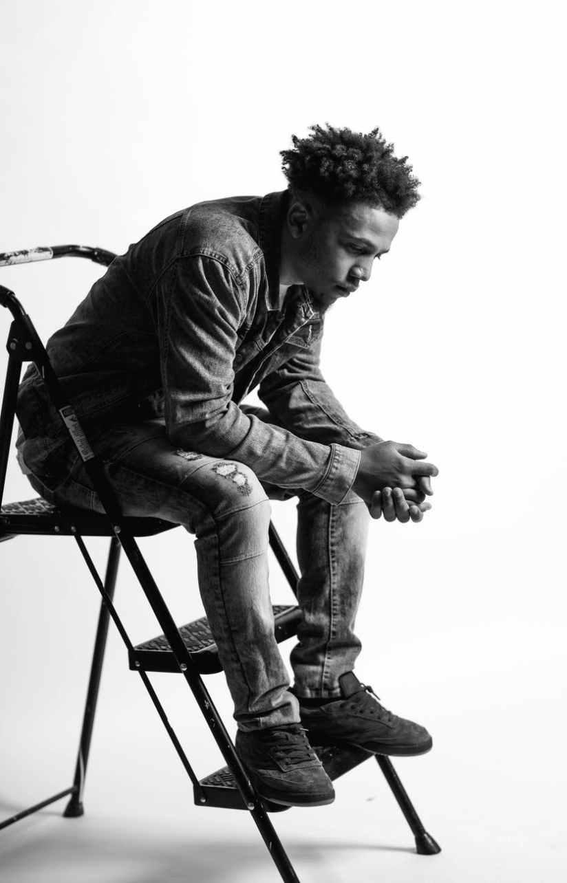 monochrome photo of man sitting on ladder